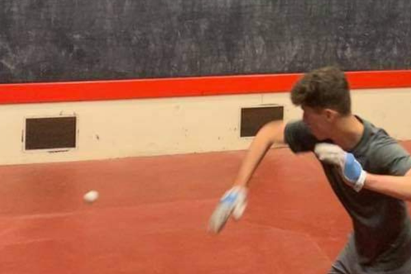 One player on a rugby fives court preparing to hit a ball